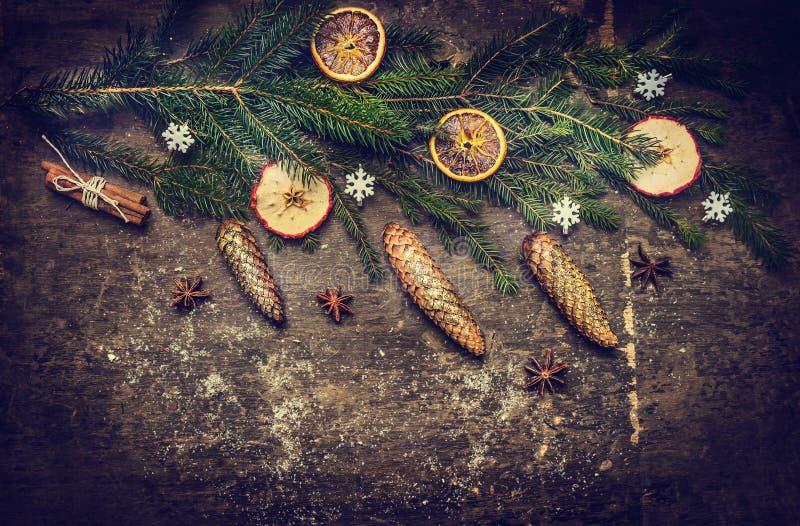 Julkortet med gran förgrena sig med kottar på mörk lantlig träbakgrund royaltyfri bild