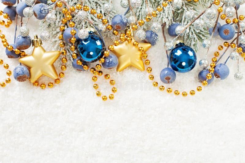 Julkortgr?ns Xmas-sammansättning med den gröna granfilialen, guld- stjärnor, blåa struntsaker och bär på vit snöbakgrund royaltyfri fotografi