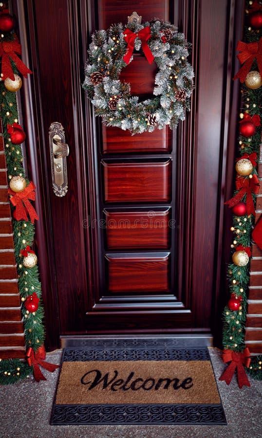 Julkrans med garneringar på dörren - välkommen dörrmatta arkivfoto