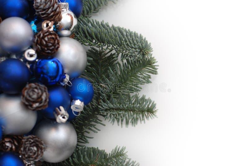 Julkrans med granfilialer blått- och silverbollar eller Cristmas jordklot som dekoreras med Pinecones Isolerat med kopiera utrymm arkivbilder