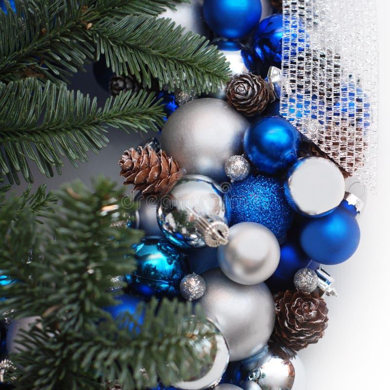 Julkrans med granfilialer blått- och silverbollar eller Cristmas jordklot som dekoreras med Pinecones Isolerat med kopiera utrymm royaltyfri fotografi