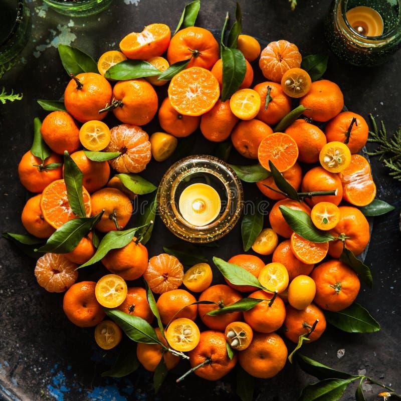 Julkrans med mandariner, kumquaten och gräsplansidor på ett b royaltyfri fotografi