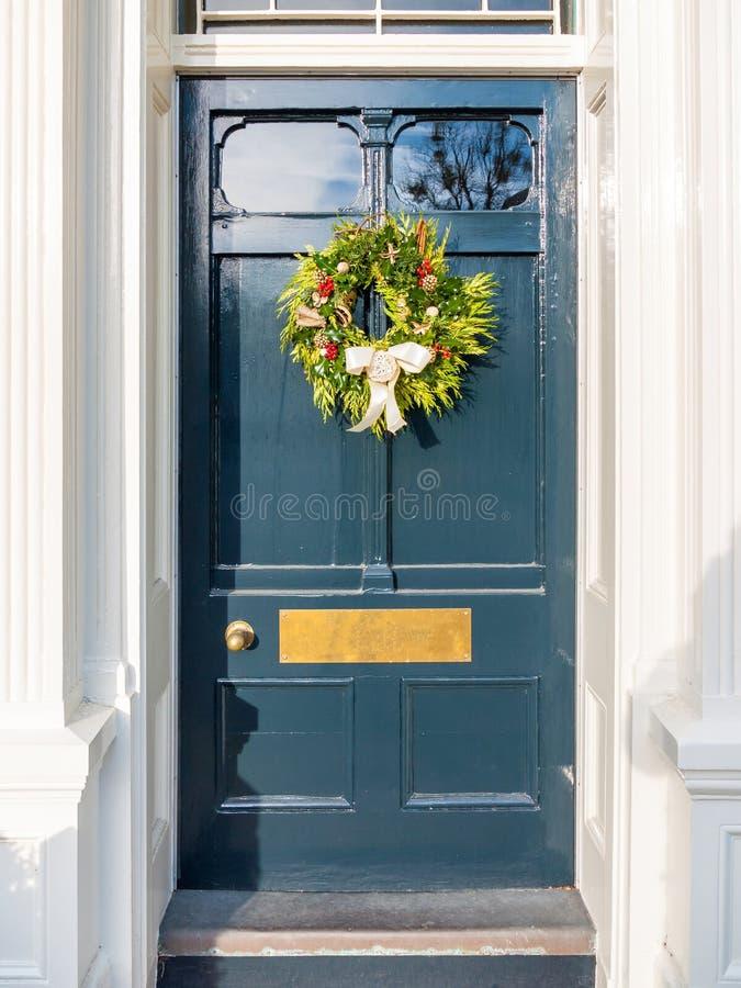 Julkrans på blått landsytterdörrhus royaltyfria bilder