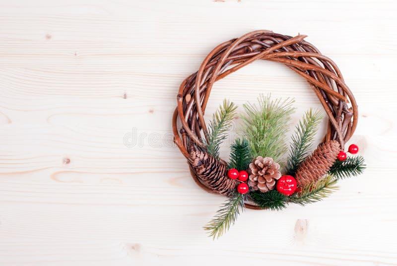 Julkransen av ris med sörjer visare och kottar på ljus b royaltyfri foto