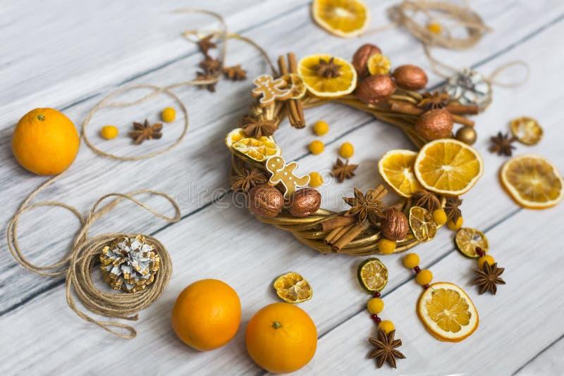 Julkransen eller kransen för nytt år som gjordes av guld- filialer och valnötter, pinnar av kanel, blommor av badian eller anis,  royaltyfri bild