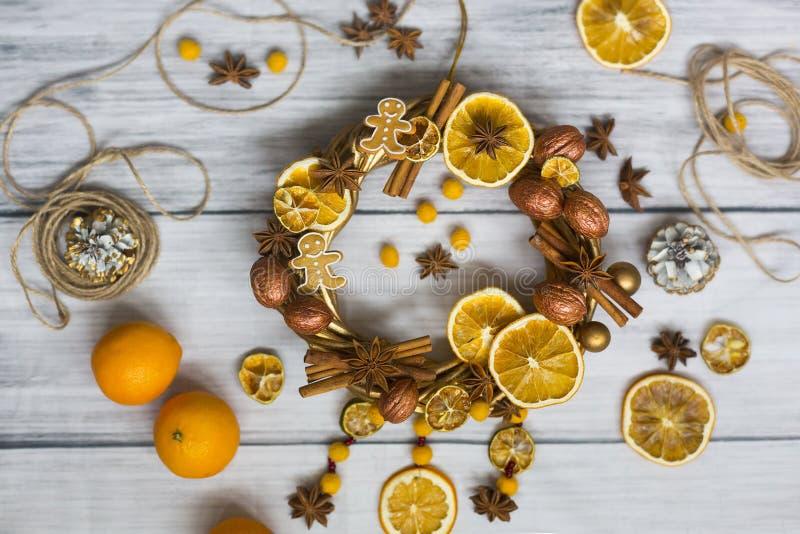 Julkransen eller kransen för nytt år som gjordes av guld- filialer och valnötter, pinnar av kanel, blommor av badian eller anis,  royaltyfri foto