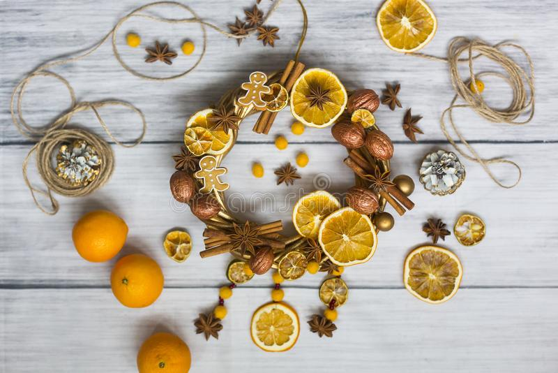 Julkransen eller kransen för nytt år som gjordes av guld- filialer och valnötter, pinnar av kanel, blommor av badian eller anis,  arkivfoton