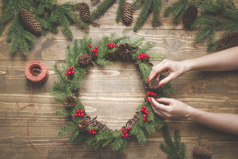 Julkransen som göras av gran, förgrena sig med järnekbär på träbräde Kvinnlig hand dekorerad krans Top beskådar fotografering för bildbyråer