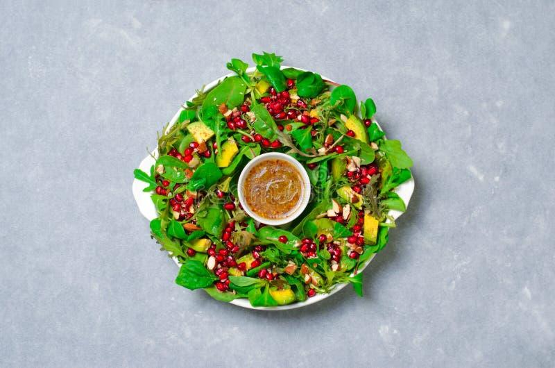 Julkranssallad med granatäpplet, avokadot, salladblandningen, mandeln och densenap dressingen, sunt äta royaltyfria foton
