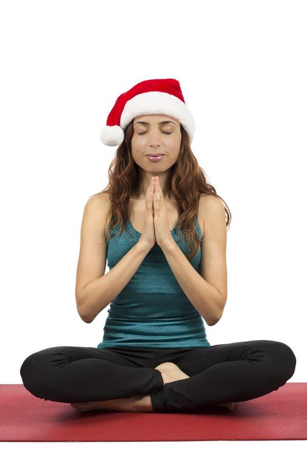 Julkvinna med den santa hatten i meditation royaltyfri foto