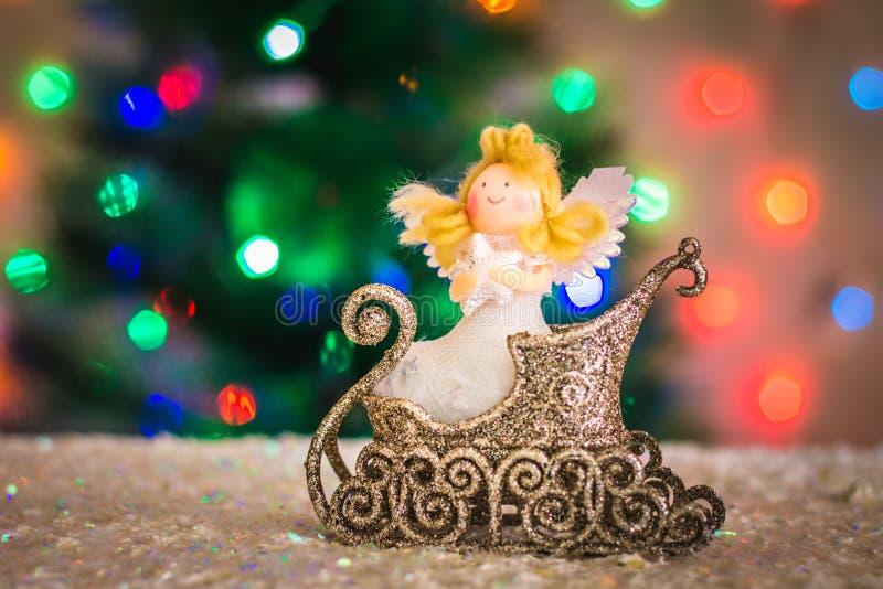 Julleksakängel i en släde mot bakgrunden av en julgran, ljus av girlander, bokeh royaltyfria foton