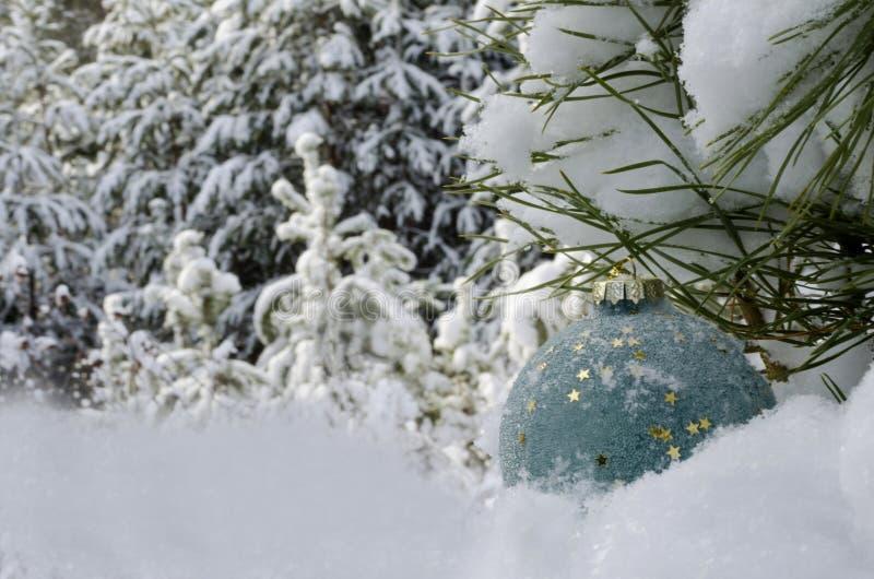 Julleksak i snön mot vinterskogen arkivbilder