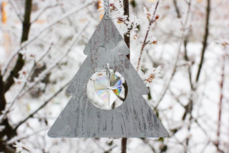 Julleksak som hänger på ett träd i vinter arkivbild