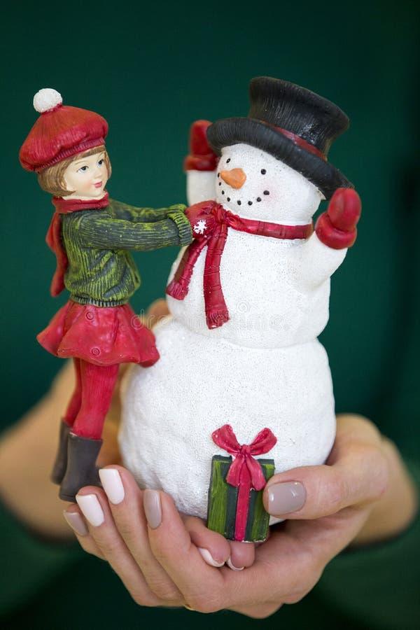 Julleksakflicka och snögubbe i kvinnlighänder på en grön backgr royaltyfria foton
