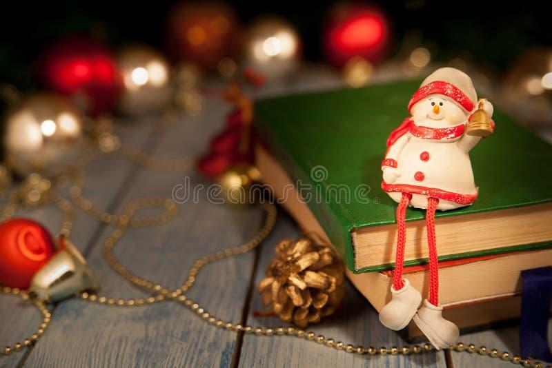 Julleksaksnögubben håller ett klockasammanträde på böcker royaltyfria bilder