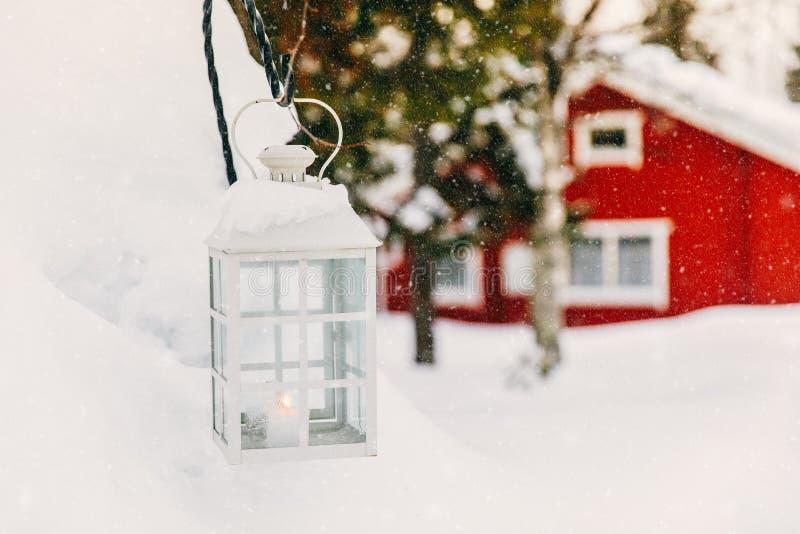 Julljus i lykta Röd trästuga i lantliga snöig Finland royaltyfri fotografi