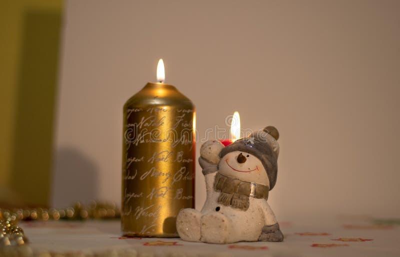 Julljus med ett diagram av en gullig snögubbe arkivfoto