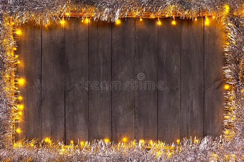 Julljus på en träbakgrund med fritt utrymme Ram med silverjulkedjan arkivbilder