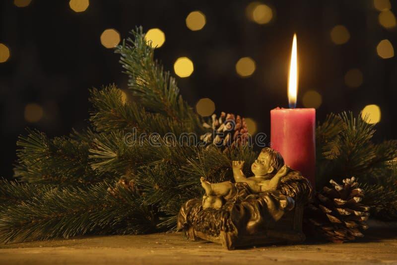 Julljuset med statyetten av behandla som ett barn Jesus arkivfoto
