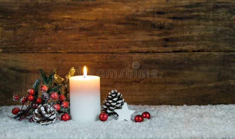 Julljusgarnering med sörjer kotten, granträdet, röda bär, stjärnan och röda julstruntsaker arkivbild