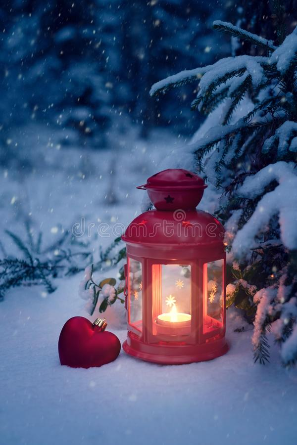 Jullykta under trädet med en gåva i träna Julhelgdagsafton i träna Jul lykta och leksakhjärta i snön royaltyfri foto