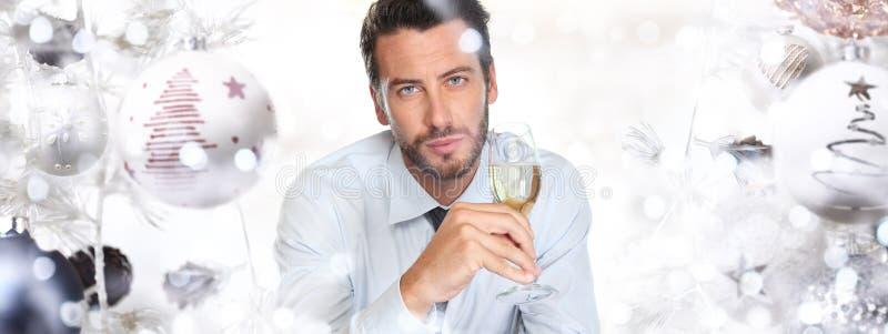 Julmannen dricker ett exponeringsglas av mousserande vin på bollträdbac royaltyfria foton