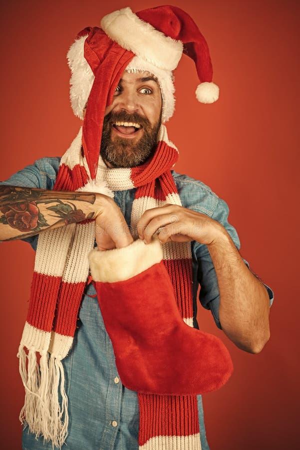 Julmannen satte handen i xmas-strumpa på röd bakgrund arkivbild