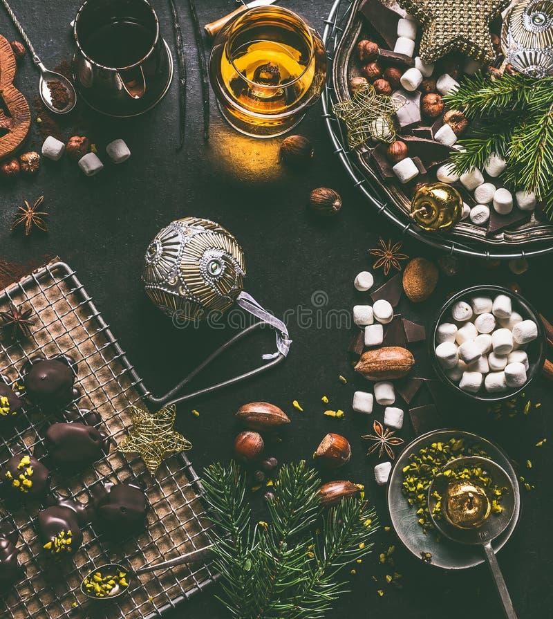 Julmatbakgrund med choklad, marshmallowen, kakor, hemlagade brända mandlar, kakao, muttrar och andar arkivfoton