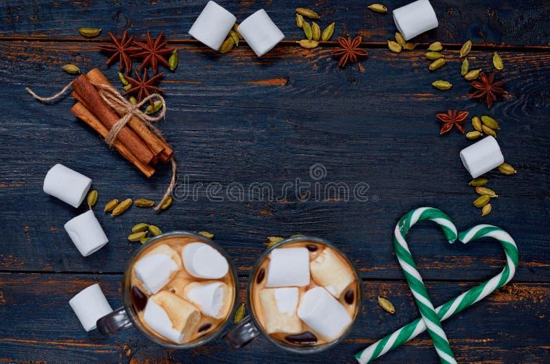 Julmatbakgrund med kopieringsutrymme Ram av varm choklad med marshmallower, hjärtor av godiskottar och vinterkryddor arkivbild
