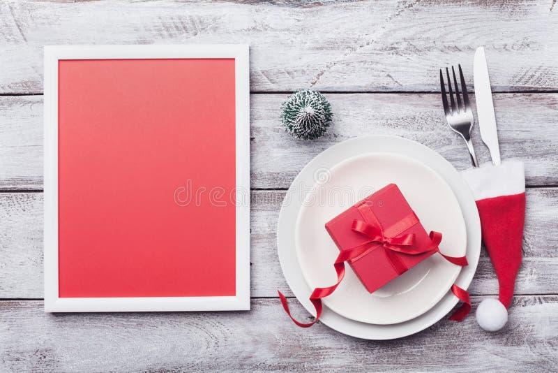 Julmodell för ferietabellinställning Bildram, gåva, granträd, vit platta och bestick på lantlig bästa sikt för tabell arkivbilder