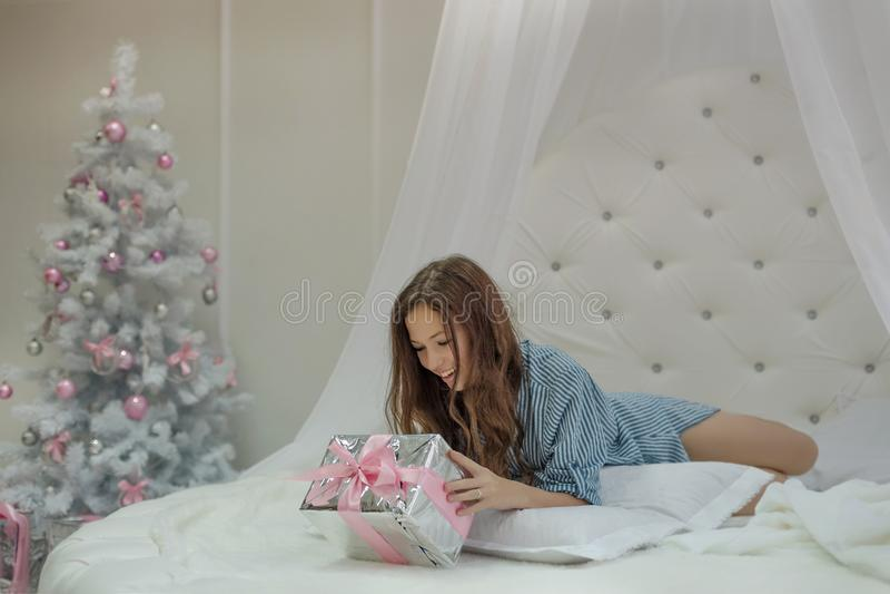 Julmorgonen vaknar finner flickan upp och en gåva för nytt år i hennes säng, och hon är förvånad och lycklig på jul royaltyfria bilder