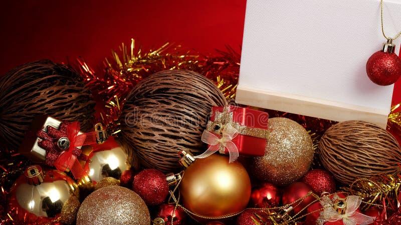 Julobjekt i rött och guld- tema med anseendet för det vita brädet för skriver formuleringar royaltyfri bild