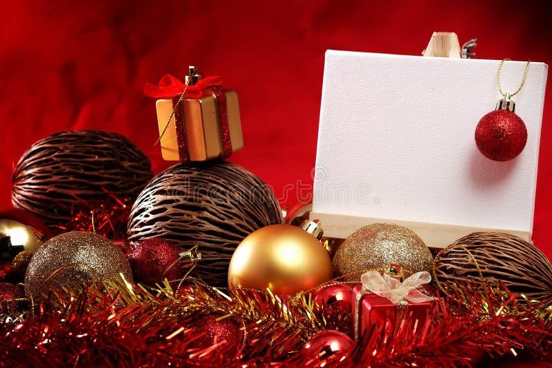 Julobjekt i rött och guld- tema med anseendet för det vita brädet för skriver formuleringar arkivbilder