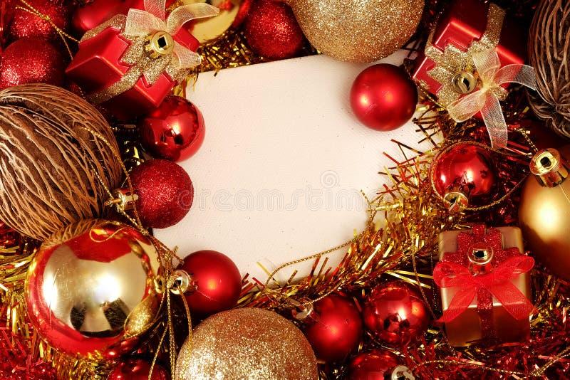 Julobjekt i rött och guld- tema med den vita ramen för skriver ord arkivfoton