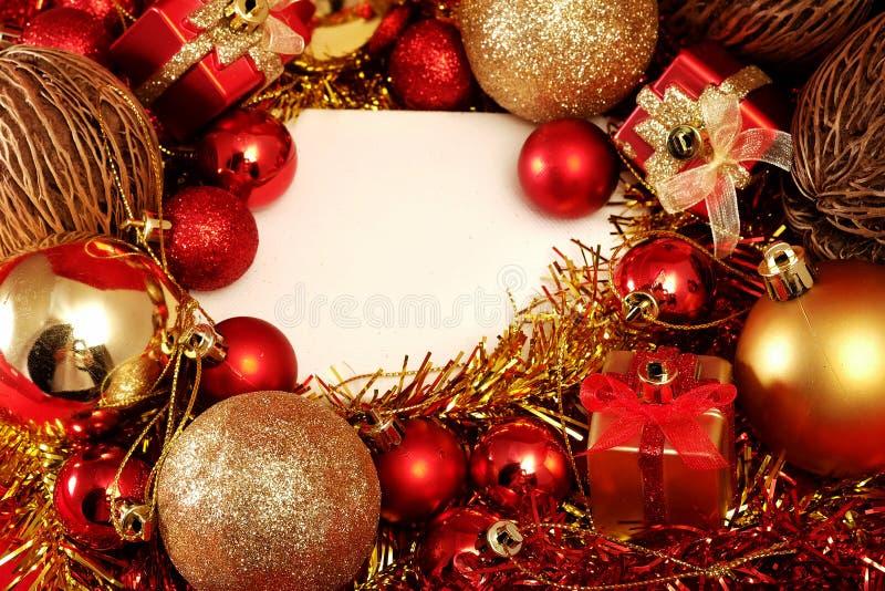 Julobjekt i rött och guld- tema med den vita ramen för skriver ord royaltyfri fotografi