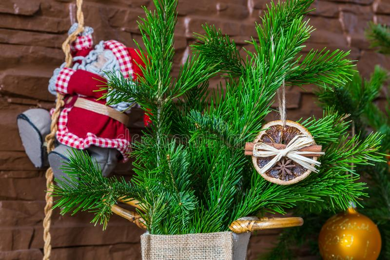 Julordningen av torra orange skivor och kanelbruna pinnar och Santa Claus klättrar repet arkivfoton
