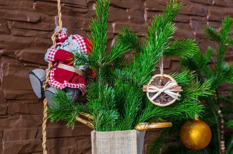 Julordningen av torra orange skivor och kanelbruna pinnar och Santa Claus klättrar repet royaltyfri bild