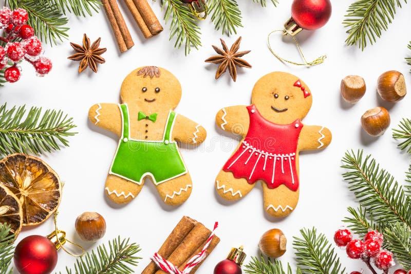Julpepparkakakakor, kryddor och garneringar på vit arkivfoto