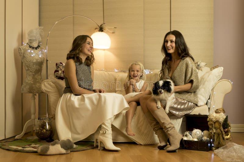 Julphotosession med två flickor, ett barn och en hund i varm ljus studio royaltyfria foton