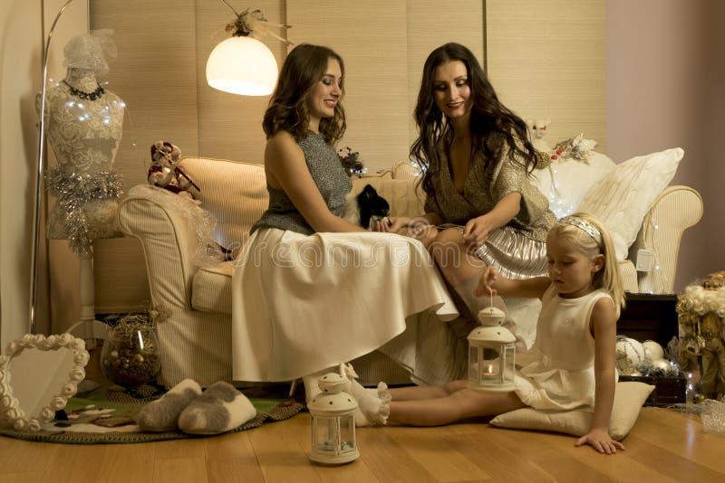 Julphotosession med två flickor, ett barn och en hund i varm ljus studio fotografering för bildbyråer