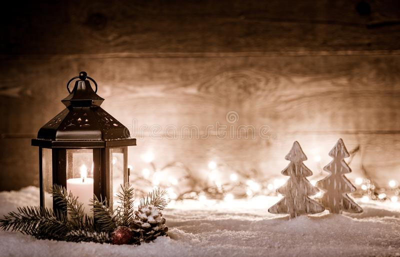 Julplats med en lykta, träd, en granfilial, snöflingor och suddiga ljus framme av ett upplyst mörkt träbräde som arkivfoton