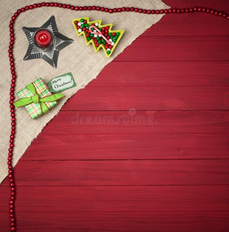 Julplatsen med den lantliga röda brädebakgrunds- och trädgodismaträtten, slogg in gåva med namnetiketten för glad jul Det är squa arkivfoton