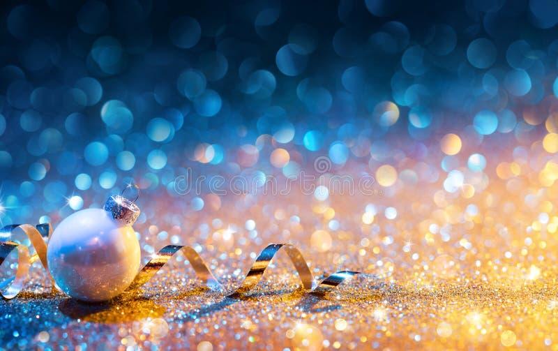 Julprydnader på Glitter - Bokeh guld- blått med bollen arkivbild