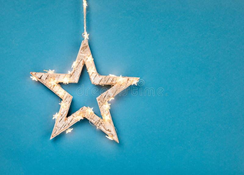 Julprydnadstjärna som slås in i ljus på blått arkivbilder