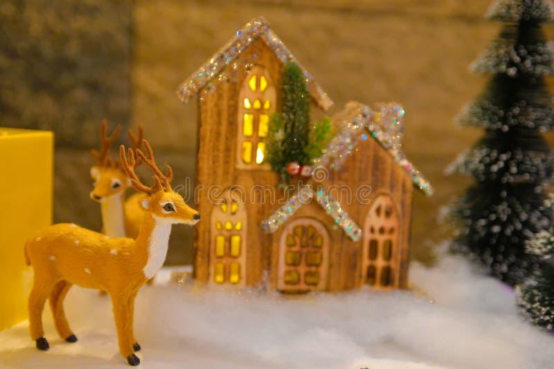 Julpynt, fluffig ren, mycket liten trä och tänd stuga royaltyfri bild