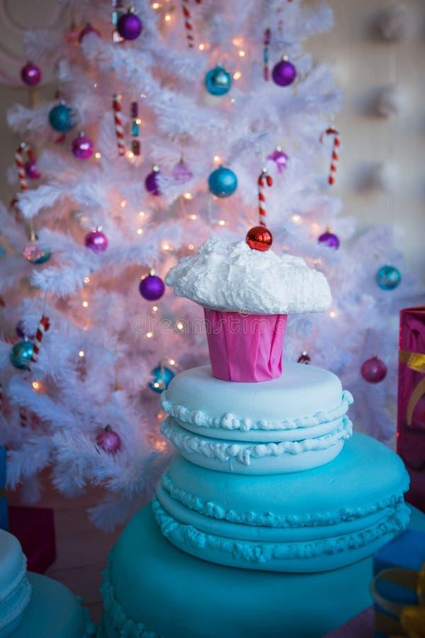 Julpynt i form av kakor och stor choklad Julleksaker på en vit konstgjord julgran royaltyfri fotografi