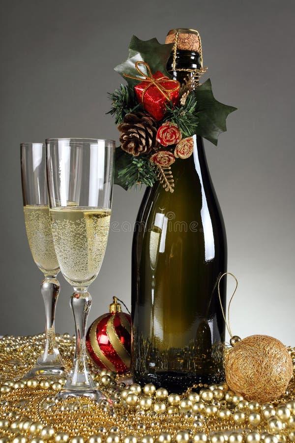 Julpynt och en champagneflaska arkivfoton