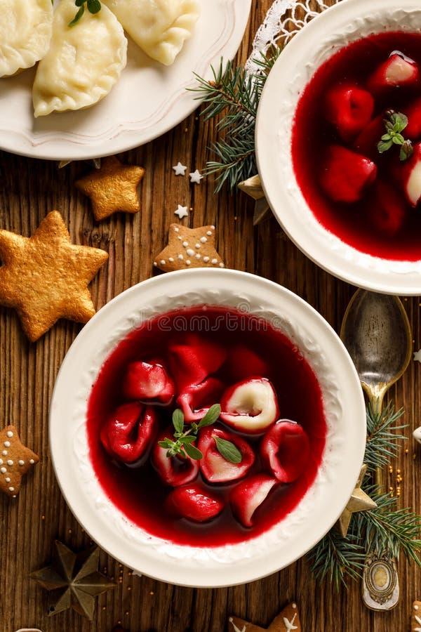 Julrödbetasoppa, borscht med små klimpar med champinjonfyllning i en keramisk bunke på en trätabell, bästa sikt royaltyfri bild