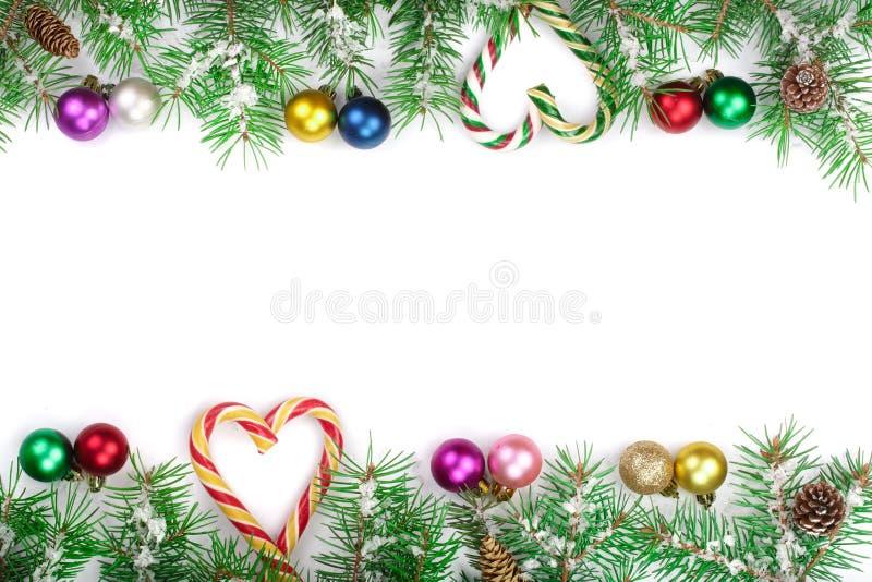 Julram av granträdfilialen med godisrottingar och bollar som isoleras på vit bakgrund med kopieringsutrymme för din text royaltyfri bild