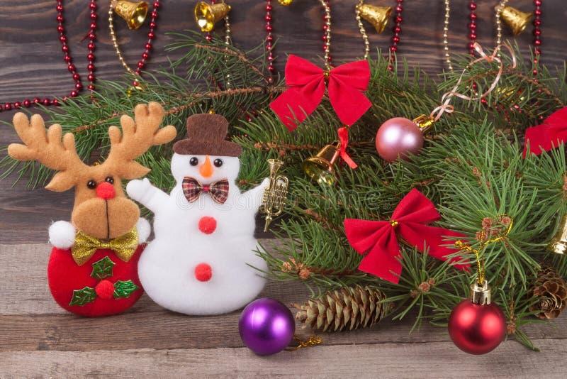 Julsammansättning av dekorerade granfilialer bugar och klumpa ihop sig med snögubberenen på en träbakgrund royaltyfria bilder